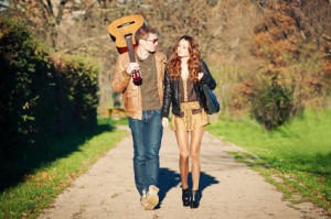 Young couple walking in a romantic mood with guitar outdoors in