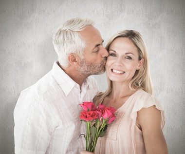 Affectionate man kissing his wife on the cheek with roses