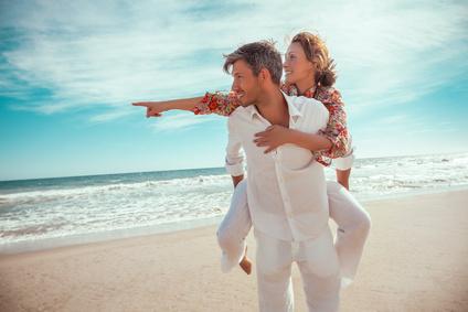 frau zeigt reise ziel am strand zum sommer urlaub