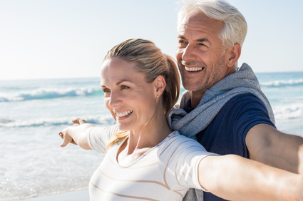 Happy senior couple standing on beach with arms outstretched and looking away. Happy couple at beach on a bright sunny day. Retired husband and smiling wife thinking about their future.