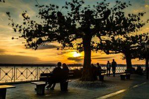 Älteres Paar sitzt bei Sonnenuntergang am See