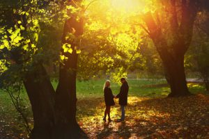 Beautiful young couple walking in the autumn park. The man with tenderness hugs woman.