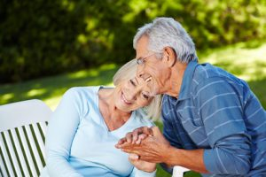 Zwei verliebte Senioren sitzen gemeinsam im sommerlichen Garten